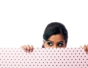 kozzi-beautiful-young-woman-hiding-behind-a-pink-and-black-dotted-wall-441x294-378x294