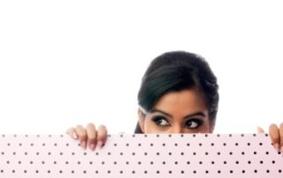beautiful young woman hiding behind a pink and black dotted wall
